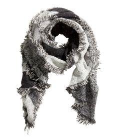 Gris/noir. Écharpe frangée en tissu souple. Dimensions 60x200 cm.
