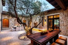 This beautiful house in San Diego features a Mediterranean design and it has a magnificent old tree in the center of the patio.