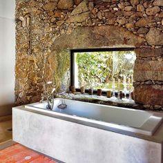 Bañera encastrada en una estructura de cemento pintado al estuco