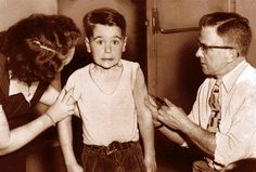 """Kurt Achenbach, 7, a first-grader at Baker School in 1954, bucks up his courage as he gets a shot from Dr. Frank Prather. Young Kurt was one of 1.8 million """"polio pioneers"""" who volunteered to test the Salk vaccine."""