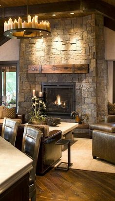 A cozy rustic family room features leather furniture, reclaimed wood floors and beams, a stone fireplace, and a wonderful candle-studded chandelier. (via John Kraemer & Sons) Rustic Fireplaces, Home Fireplace, Fireplace Design, Stone Fireplaces, Fireplace Ideas, Fireplace Lighting, Fireplace Remodel, Farmhouse Fireplace, Fireplace Inserts