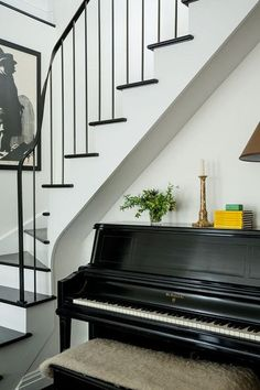 Replacing the steel spiral staircase with a gracefully curving formal stair imbued the urban flat with a family-home sensibility. Owner Trevor Winstead's treasured piano completes the scene.
