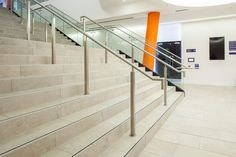 Fantastic University design, featuring bright orange colours and natural stone tiles. Image shows staircase.
