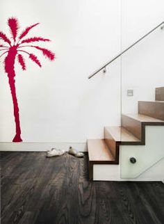 The staircase going to the top level is ultra-modern and unique. The combination of wood and glass create a warmth as well as a grounding feeling, whilst the colorful wall decoration of the pink palm-tree brings a touch of vibrancy to the interior. by Platform 5 Architects LLP