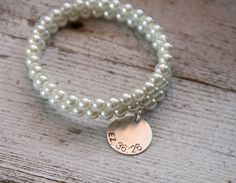 This is an old classic that we've brought back, due to popular demand. A coil bracelet is strung with glass pearls on steel memory wire, to create a simple design that can be worn any time.  The bracelet has no clasp, which makes it great for people who have trouble with clasps.  Just wrap it around the wrist and it stays put!  The shape will spring back for years and years.  This one is finished with a sterling charm, stamped with your favorite Bible verse.  Just mentio...