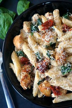 Overhead shot of a black plate of Chicken alfredo penne pasta with sun-dried tomatoes and spinach