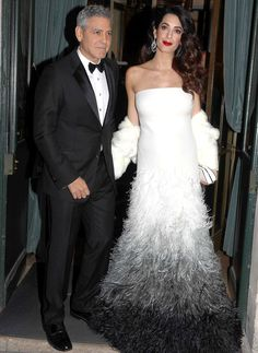 Amal Clooney hit the red carpet  at the César Awards in Paris, in a custom strapless white  Atelier Versace gown with a feathered skirt in fading shades of gray. She completed her look with art deco -style earrings