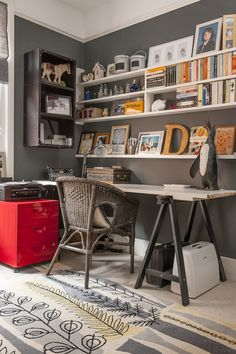 The study is painted in Farrow & Ball dark charcoal 'Downpipe'. On the white trestle table, is a terrific old Remington typewriter, another deed box and a penguin, that started life as a garden water-feature.