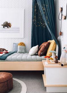 Une tête de lit en tissu et une guirlande lumineuse pour une chambre d'enfant poétique