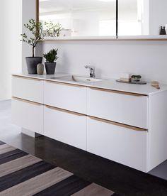 De lyse naturfarver med det hvide. Invita. Badeværelse everline natur eg modehvid. Spejlkabinet med ramme og kontrast ved skufferne der bryder det hvide.