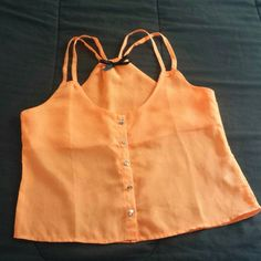 Sheer Neon orange strappy top Super cute sheer almost crop top (depends on torso) bright neon orange color. Cute racer/razor back style with double straps on both sides. Silver stud buttons.  Worn 1 time.  100% polyester. Machine wash cold, line dry.    Bundle for discounts :) No trades. Ali & Kris Tops Tank Tops