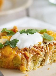 Chicken Tamale Casserole  -  1 c. shredded cheddar cheese, divided...1/3 c. milk...2 eggs...1 te. ground cumin...1/8 t. ground chili powder...1 (14 3/4 oz) can cream-style corn...  1 (8.5 ounce) box corn muffin mix...1 (4 oz) can chopped green chilies...1 (10 oz) can red enchilada sauce...2 c. shredded cooked chicken breast...1/2 c. sour cream (opt)...  cilantro (opt.)