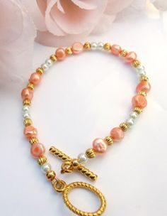 Pair this bracelet with a golden tan!  I used peach potato pearls, white glass pearls and gold beads to create this bracelet.  This bracelet is approx. 9 inches long including the clasp.  I started by