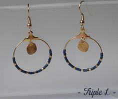 ~ DESCRIPTIF ~ Cette paire de boucles doreilles LANA est composée de créoles, de perles et dune monture en métal doré pour oreilles percées. Couleurs des perles : bleu marine - doré. Dimensions : 2,5 cm de diamètre. ~ MATERIEL UTILISE ~ - Crochets doreilles en laiton doré - Créoles en laiton doré - Perles ~ ENVOI ~ Les bijoux sont envoyés en courrier suivi dans une enveloppe en papier bulle et soigneusement emballés. ~ PRECAUTIONS DUSAGE ~ Ce bijou est fait à la main et avec soin. Les…