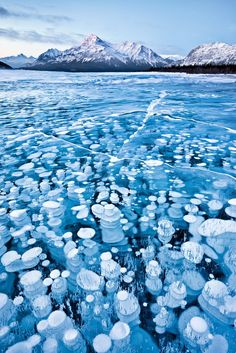 "Real - Photographed by Emmanuel Coupe, this photo shows frozen gas bubbles in a Canadian lake. In his own words: ""This image was taken in winter time in a arid area of the Canadian Rockies. Temperatures where below -30 degrees Celsius yet because there was no snow fall the surface of the lake was uncovered allowing me to see and capture the bubbles (gas release from lake bed) that were trapped in the frozen waters."""