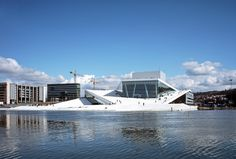 Home to the Norwegian National Opera and Ballet, the Oslo Opera House was completed in 2008 with a roof that angles to the ground, allowing visitors to walk up and experience panoramic views of the surrounding scenery. The façade is a mix of white Carrara marble, white aluminum, and glass, while the interior is covered in warm oak.