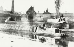 BW192-3-2-2-13-1-280 Narrowboat stranded on the canal bank in Brentford due to flooding Description Black and white photograph looking across the canal, shows the Fellows, Morton & Clayton Limited (FMC) narrowboat 'Amesbury' stuck on the bank with a boat family at the stern. The FMC narrowboat 'Seal' is on the canal in front of 'Amesbury', there are boat people on the cabin including Mrs Walley. Industrial buildings and Brentford School can be seen in the background. Date 1932