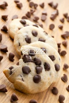 chocolate chip cookie - A close-up vertical image of chocolate chip cookies on a wooden table