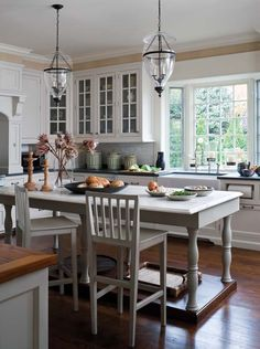 Light and beautiful kitchen! Love the large table used as an island instead of a boxy, closed off island.
