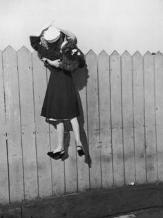 A sailor leans over a picket fence and lifts his girlfriend up for a kiss, 1945.(Photo by FPG/Hulton Archive/Getty Images)