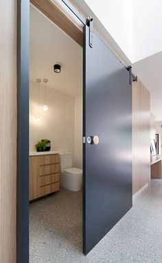 A Contemporary Update For A Brick House In Melbourne In the main floor of this modern renovated house, a central timber-clad pod has matte black sliding barn doors that conceals various rooms, like a small bathroom and cloak room. Brown Brick Houses, Bathroom Doors, Bathroom Ideas, Bathroom Black, Barn Bathroom, Black Bath, Bathroom Modern, Small Bathrooms, Bathroom Remodeling