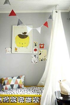 decoração quarto de bebê com bandeirinhas de tecido vermelha preta e branca pendurada no teto acima do berço