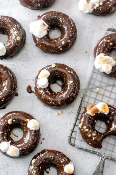 S'mores Donuts - This donut recipe is made lighter and easier with baked donuts! They're dipped in a silky chocolate ganache, and topped with graham cracker crumbs and toasted marshmallows - delish! #donuts #donutrecipe #baking #dessertrecipes #summerrecipes #smores #smoresrecipe #bakingrecipe   bluebowlrecipes.com
