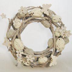 Proutěný velikonoční věnec světle šedý je dozdoben plastovými křepelčími vajíčky v bílé barvě a dřevěnými Motýlky a kytičkami. Věnec lze snadno zavěsit na vchodové dveře a příjemně tak umocní čas Velikonoc v klasické i moderní domácnosti. Průměr proutěného věnce je 22 cm.