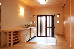 天板にカエデを使い、オリジナルで作り付けた下駄箱や小窓が印象的。右側は大容量の物入れになっている。
