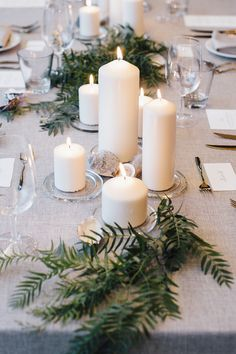 Coastal wedding reception centrepiece of pillar candles, shells and greenery on grey linen | Alexandra Strong