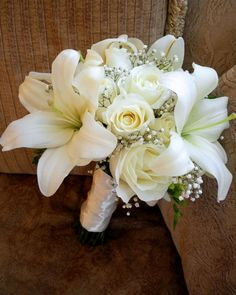 This natural touch bouquet features cream/white calla and tiger lilies, roses and rosebuds accented by silk lily of the valley and snow balls and an ivory silk partial stem wrap with a pearl seam.