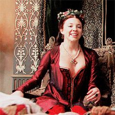 She looks so happy here. Even though he would always feel very jealous and sad seeing her up on the throne next to Henry, moments like this would ease his pain. She looks so happy and excited, and while he would like to have caused these emotions himself, he wouldn't be able to help but smile regardless. He would very much wish to be in Henry's spot right now. The red looks beautiful and festive on her, which only adds to her magnetism, and her hair is in his favorite style, elegant and…