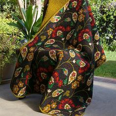 "Cotton floral throw.  Product: ThrowConstruction Material: CottonColor: Green and multiFeatures: Floral print face reverses to solid green backDimensions: 50"" x 60"" Cleaning and Care: Machine washable"