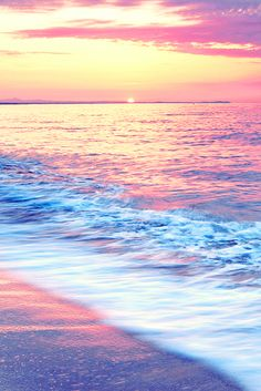Beautiful coral sunset and light blue waves coming into shore. Click here to shop beachwear by Matthew Williamson.