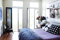 This dreamy bedroom in hues of indigo, cobalt and amethyst is drenched in sunlight, making the cool palette seem warm and relaxing. Cushion-cover graphics are visually appealing, while the impressive framed photo gives the room an up-to-the-minute look.