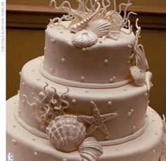The Cake    The newlyweds cut a three-tier cake with pearly white fondant covered in polka dots and white chocolate shells and coral.