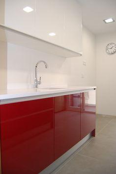cocina con mueble rojo y encimera de silestone en blanco.