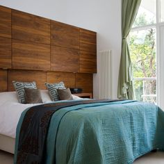 Built-in bed storage  Wood panelled headboard makes a stylish statement while disguising a series of cupboards