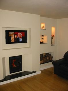 Inset stove with TV above. Also like the recessed shelving with wood store.
