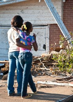 Caitlin Moore, spends a moment with her mother, Tiffaney, outside their family's damaged home. (Photo: Laura Reinhardt/World Vision)