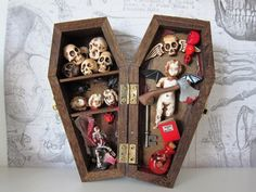 This is a 6 wood coffin shadow box. Inside is a gruesome display of skull, doll heads (with flies around them) a tormented skeleton with a devils