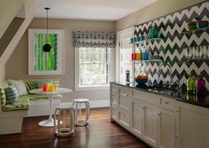 I love using graphic black and white to anchor a space. It's always a home run. In this kitchenette, I used black and white to anchor the space and then added pops of color with accessories, upholstery, and art.