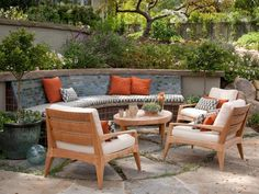 A built-in bench hugs the inside of a wall, conserving space on this terrace and maximizing seating when there's a crowd. Notice how the houndstooth on the pad is echoed in the throw pillows, and how the simple presence of an oval table (how often do you see those on a patio?) makes the space feel distinctive.