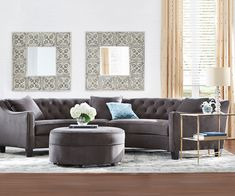 A glamourous curved sofa offers a unique shape. A perfect complement to it is a large round ottoman. HomeDecorators.com
