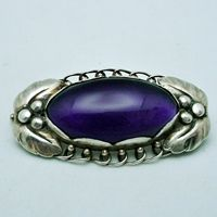 Georg Jensen. Design No. 223 B. Brooch, 830 silver with amethyst. Stone setting with 8 scalloped edges.