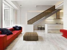 """Oszczędny w wykończeniu, a zarazem bardzo nowoczesny salon. Stolik kawowy jak i zabudowa poręczy schodów wykonana została w dekorze """"Dąb dziki Tabac"""" (R 3216)."""