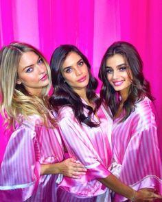 Martha Hunt, Sara Sampaio e Taylor Hill posam para fotógrafos usando o roupão rosa da marca de lingerie