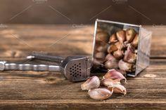 #Garlic press  Garlic press and garlic clove on wooden table