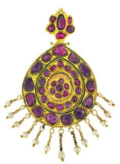 A Persian 19th century ruby and enamel pendant. The pear shaped plaque set with rows of vari-cut rubies in closed-back mounts to a similarly-set surmount, suspending a wirework fringe with pearl terminals, the reverse with pink, blue and green enamel floral motifs.