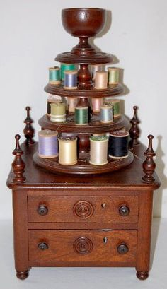 Ornate Walnut Sewing Cabinet, Table Model: 2 locking drawers with a 4 tier top spindle - 3 of those tiers hold spools of thread with the 4th one being goblet shaped to hold pins & other small items; Carved knobs, carved drawer & back panel decoration, corner spires & bun feet.